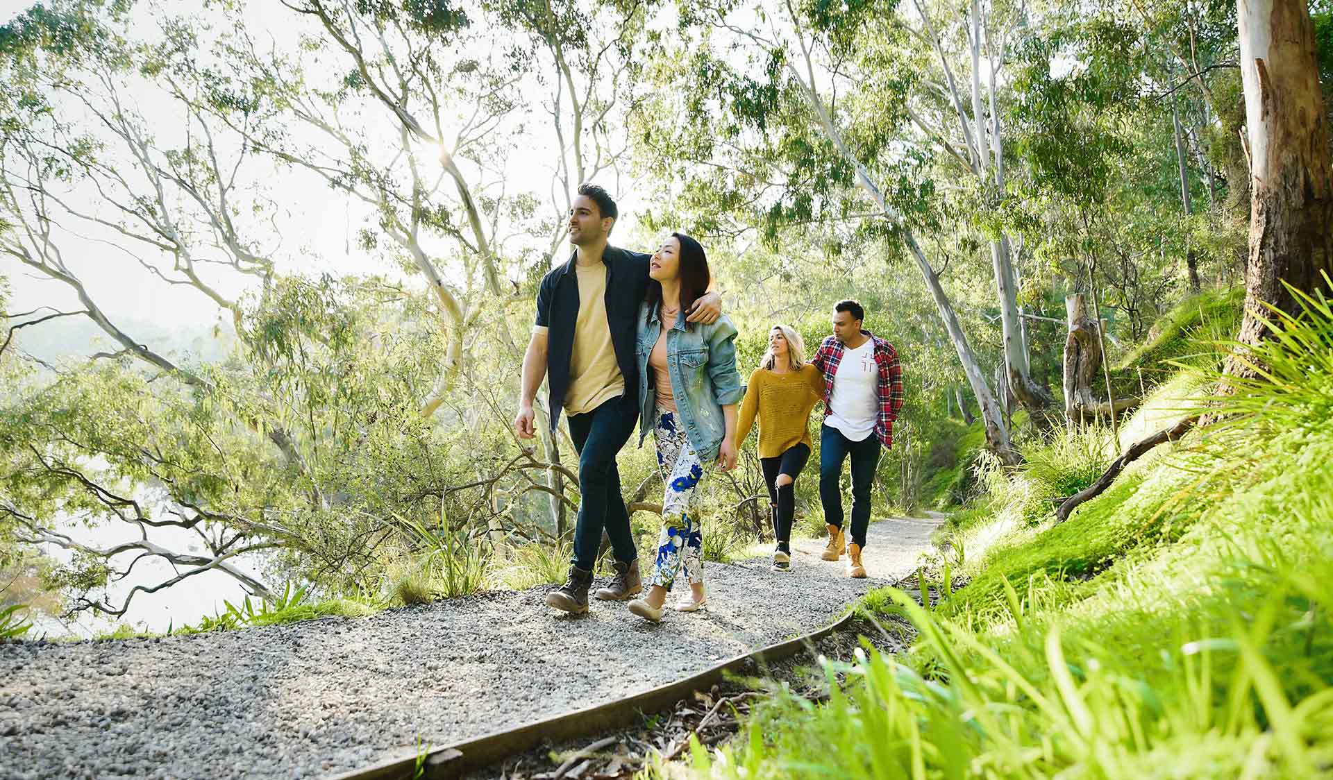 Four friends walk alongside the Yarra River through Yarra Bend Park.