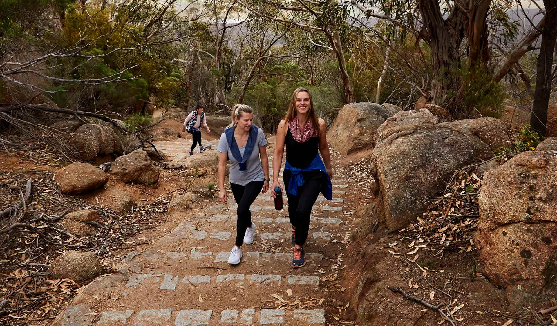 Two women in active wear walk up the granite steps on the way to Flinders Peak.