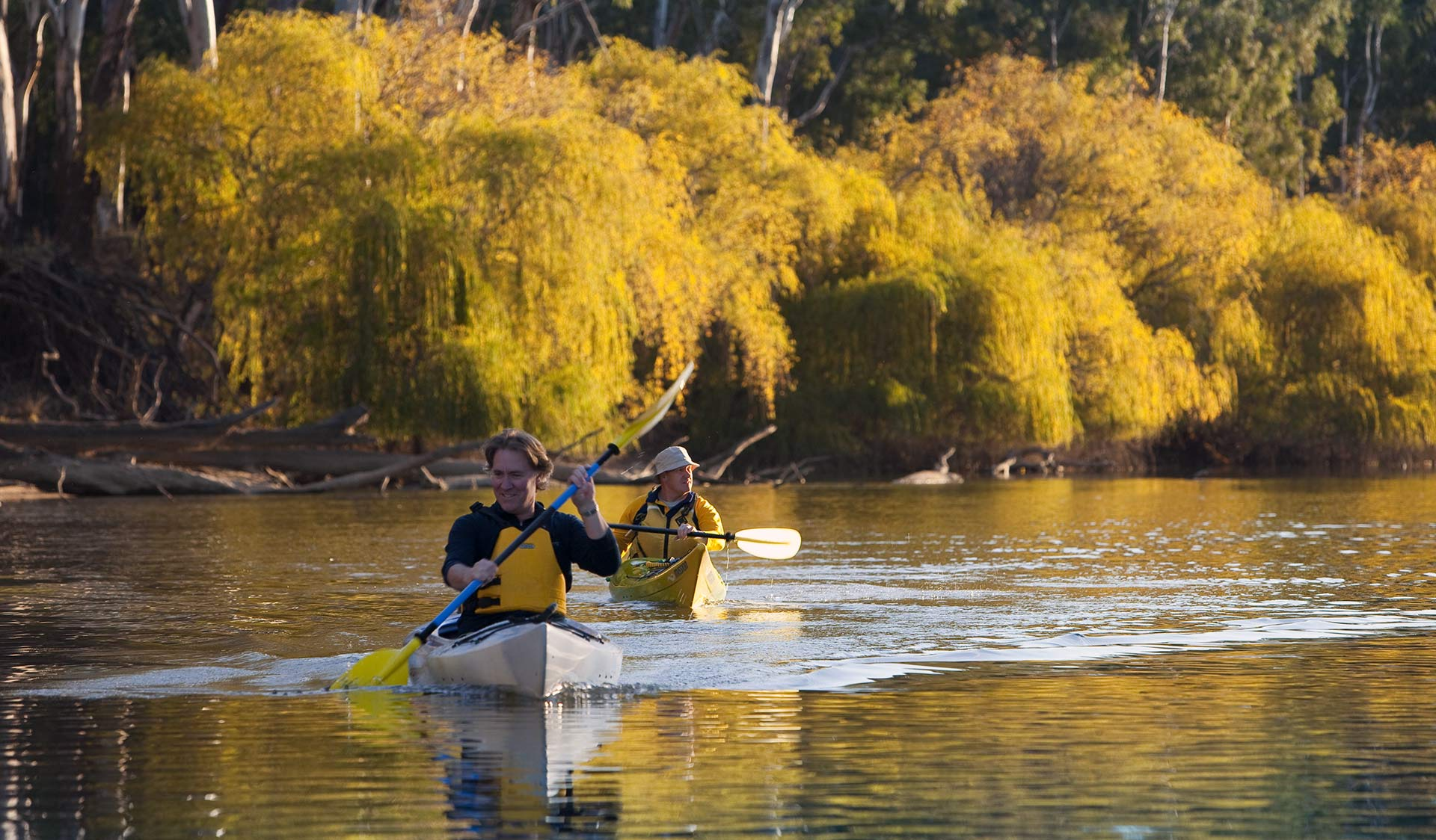 Two friends kayak along the river late in the afternoon.