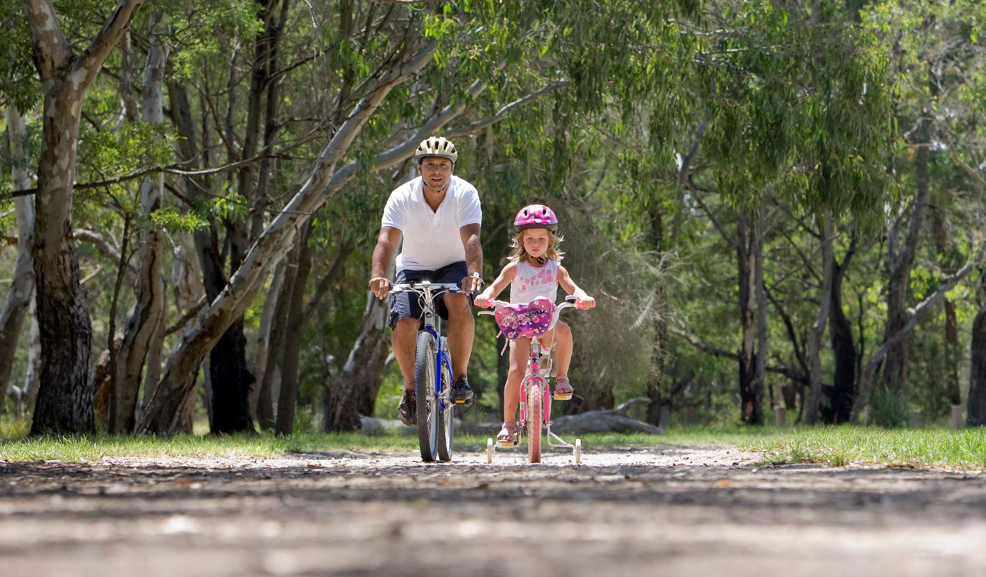 A father teaches his young daughter to ride a bike in Braeside Park.