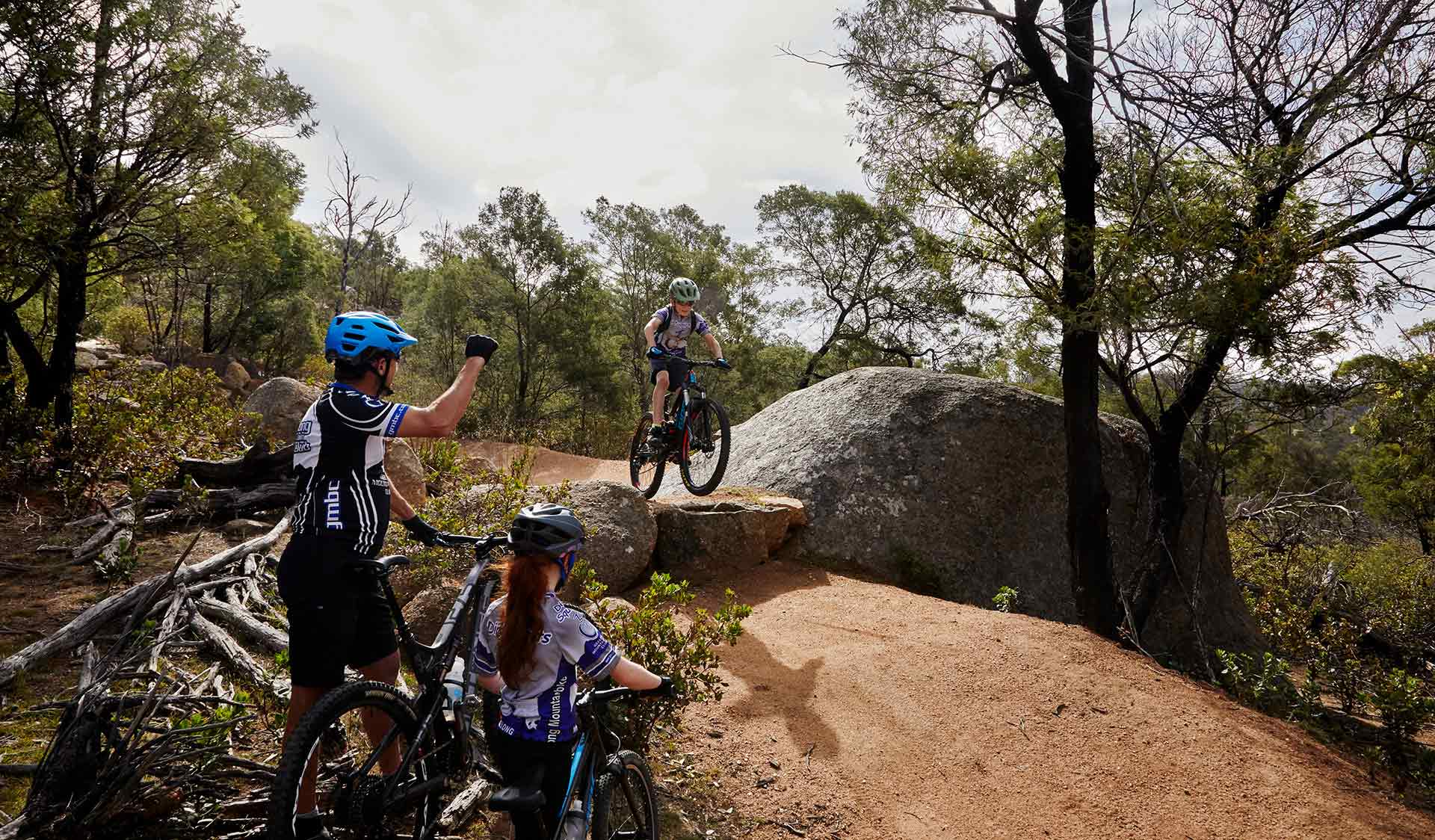 A young mountain biker attempts a drop while cheered on by his father and older sister at the You Yangs Regional Park.