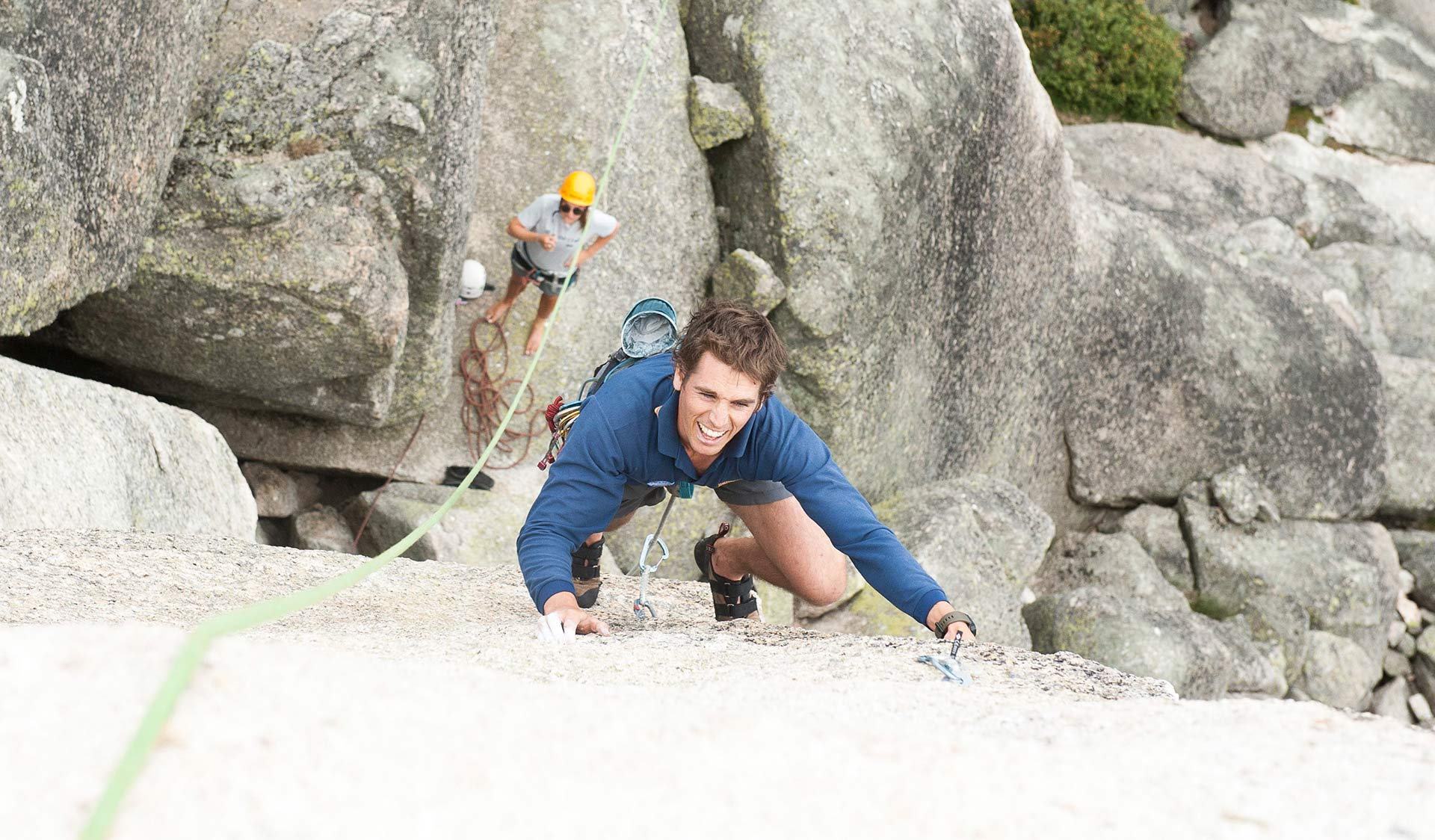 A young man climbs a near featureless wall at Mt Buffalo while his climbing partner watches on.