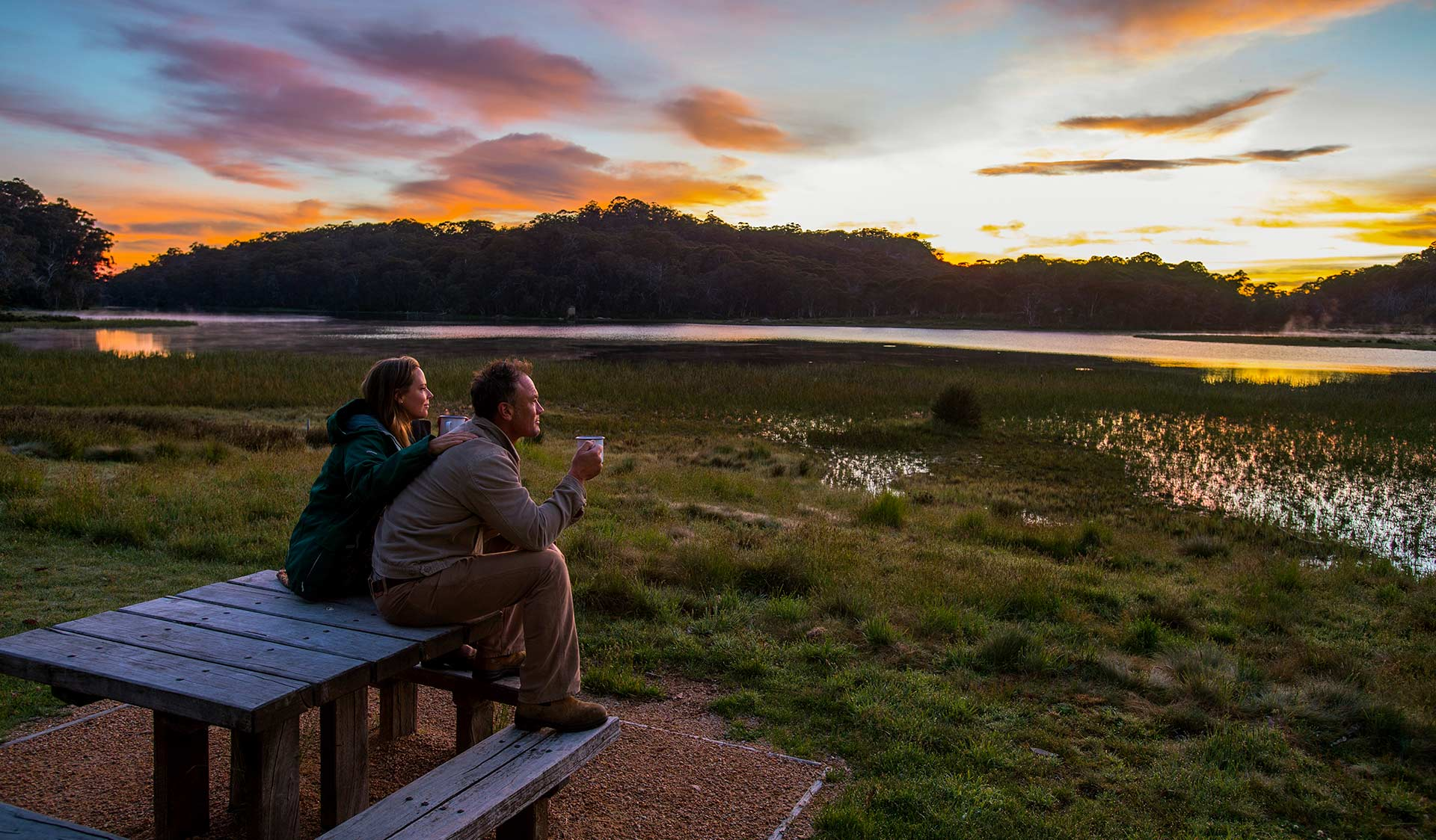 A couple watch the sunset at a picnic table on the edge of Lake Catani at Mount Buffalo National Park.