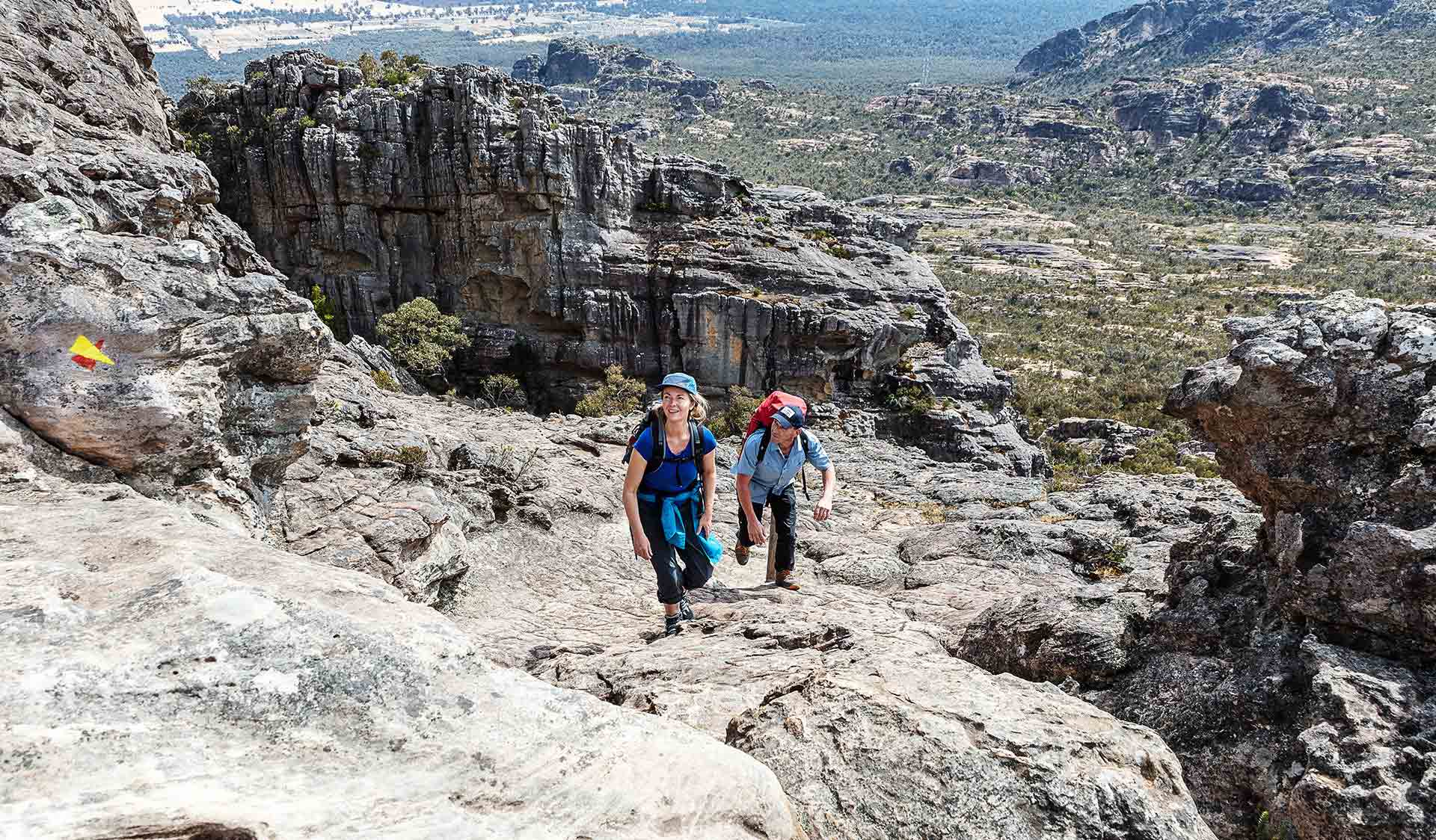 A man and woman climb up the rocky landscape of Mt Stapylton in the northern section of the Grampians National Park.